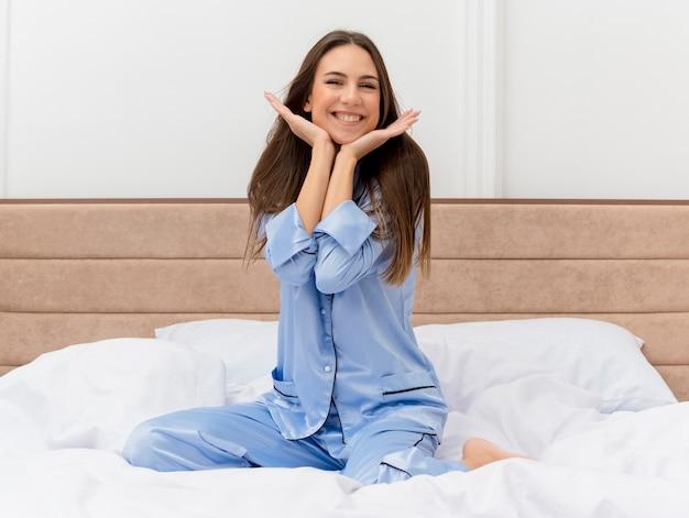 침실 인테리어에서 주말을 즐기는 행복하고 긍정적 인 미소 휴식 침대에 앉아 파란색 잠옷에 젊은 아름 다운 여자