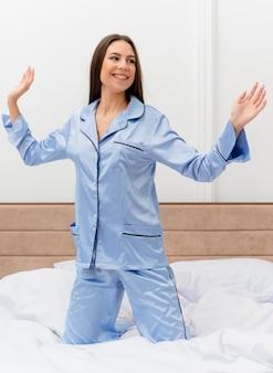 寝室のインテリアで週末を楽しんでいる幸せで前向きな笑顔で休んでベッドに座っている青いパジャマを着た若い美しい女性