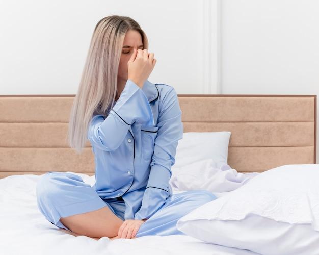 Молодая красивая женщина в синей пижаме сидит на кровати, касаясь носа между закрытыми глазами, устала и скучает в интерьере спальни на светлом фоне