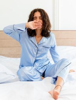 Молодая красивая женщина в синей пижаме сидит на кровати, просыпаясь, чувствуя утреннюю фатугу, зевая в интерьере спальни на светлом фоне