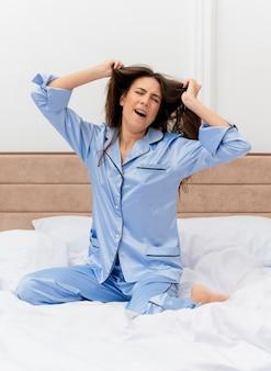 침실 인테리어에서 하품하는 아침 피로를 느끼는 streching 깨어 난 침대에 앉아 파란 잠옷에 젊은 아름다운 여자