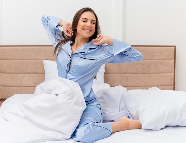 Молодая красивая женщина в синей пижаме, сидя на кровати, просыпается, протягивая руки, наслаждаясь утренним временем в интерьере спальни на светлом фоне