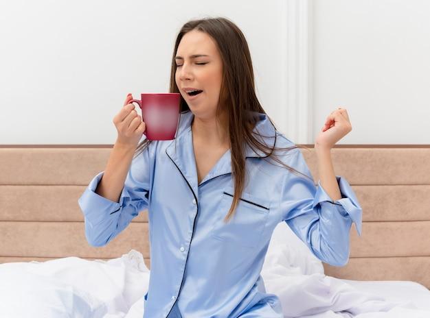 Молодая красивая женщина в синей пижаме, сидя на кровати с чашкой кофе, просыпается, зевая в интерьере спальни на светлом фоне