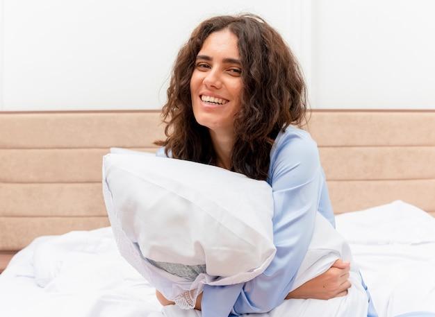 Молодая красивая женщина в синей пижаме, сидя на кровати с подушкой, счастлива и позитивно улыбается, глядя в камеру в интерьере спальни на светлом фоне