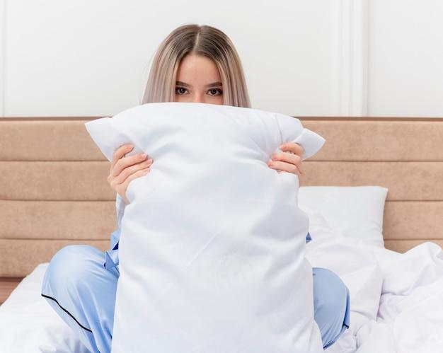 Молодая красивая женщина в синей пижаме сидит на кровати с подушкой, пряча лицо, выглядывает в интерьере спальни