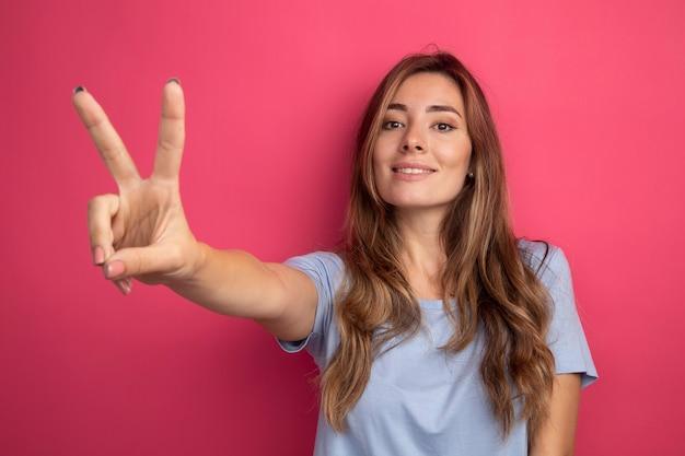 파란색 티셔츠를 입은 젊고 아름다운 여성이 얼굴에 미소를 띠고 분홍색 배경 위에 서 있는 v-sign을 보여줍니다