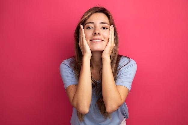 ピンクの上に立っている頬に腕を上げて幸せで前向きな笑顔のカメラを見て青いtシャツの若い美しい女性