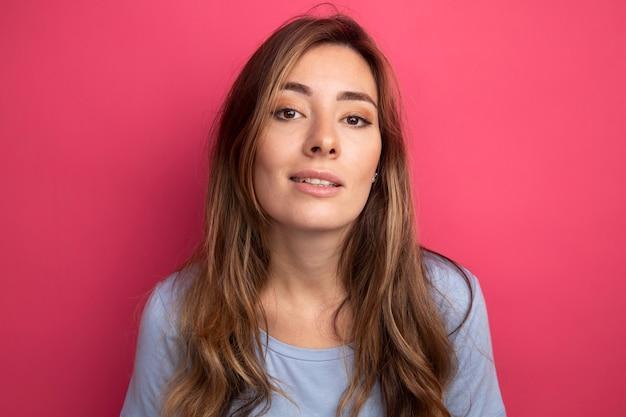 ピンクの背景の上に立って自信を持って笑顔のカメラを見て青いtシャツの若い美しい女性