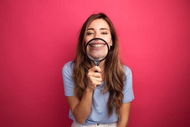 ピンクの背景の上に立って笑顔の拡大鏡を通してカメラを見て青いtシャツの若い美しい女性