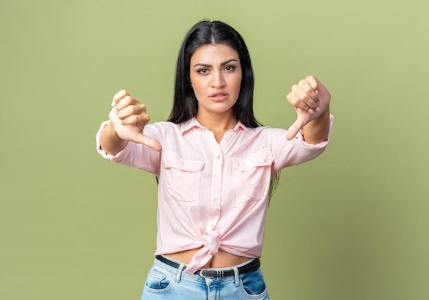 緑の壁の上に立って親指を下に見せて不機嫌なカジュアルな服を着た若い美しい女性