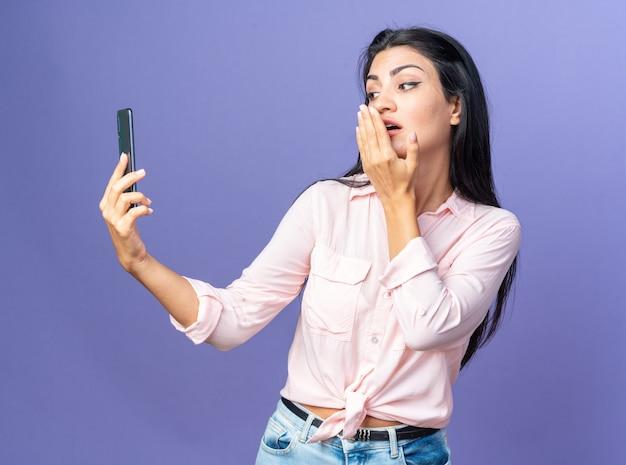 스마트폰을 사용하여 셀카를 하는 캐주얼 옷을 입은 젊은 아름다운 여성이 행복하고 긍정적인 키스를 날립니다.