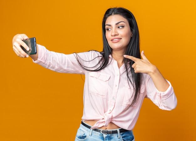 캐주얼 옷을 입은 젊고 긍정적인 여성은 주황색 벽 위에 자신감 있게 웃고 있는 스마트폰을 사용하여 셀카를 하고 있습니다.