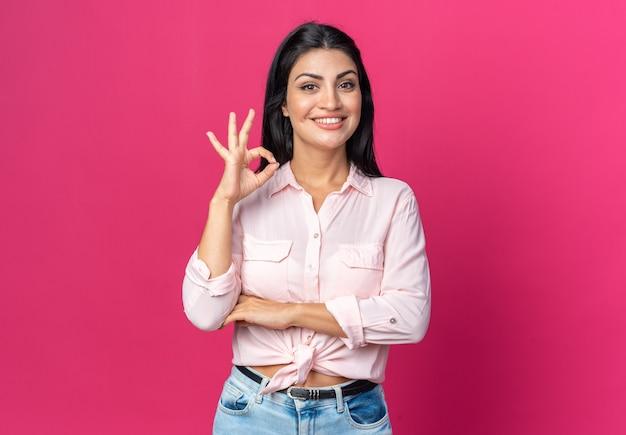 ピンクの壁の上に立っているokサインを元気に見せて幸せで前向きな笑顔のカジュアルな服を着た若い美しい女性