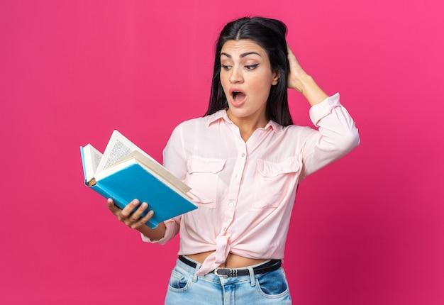 분홍색 벽 위에 서 있는 머리에 손을 얹은 채 책을 보고 있는 캐주얼한 옷을 입은 젊고 아름다운 여성
