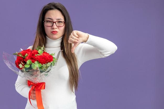 Молодая красивая женщина в повседневной одежде держит букет красных роз и недовольно смотрит в камеру, показывая большие пальцы вниз, стоя над фиолетовой стеной.