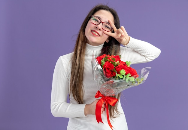 보라색 벽 위에 서 카메라 행복하고 positiveshowing v 기호 발렌타인 데이 개념을보고 빨간 장미 꽃다발을 들고 캐주얼 옷에 젊은 아름 다운 여자
