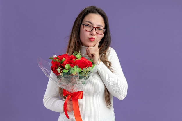 Молодая красивая женщина в повседневной одежде, держащая букет красных роз, глядя в камеру с задумчивым выражением лица, концепция дня святого валентина, стоящая на фиолетовом фоне