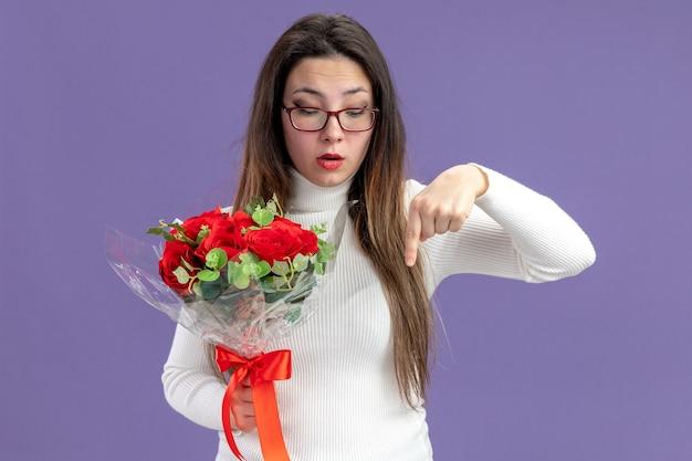 紫色の背景の上に立っている人差し指でバレンタインデーのコンセプトを指して見下ろしている赤いバラの花束を保持しているカジュアルな服を着た若い美しい女性