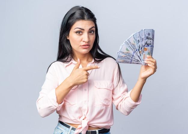 Молодая красивая женщина в повседневной одежде держит кучу долларовых денег, указывая указательным пальцем на деньги с серьезным лицом, стоящим над белой стеной