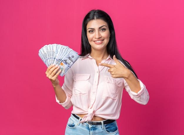 Молодая красивая женщина в повседневной одежде держит деньги, счастливая и позитивная, указывая указательным пальцем на деньги, стоящие на розовом