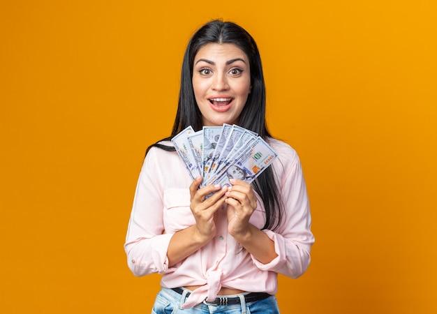 オレンジ色の壁の上に元気に立って幸せで前向きな笑顔の現金を保持しているカジュアルな服を着た若い美しい女性
