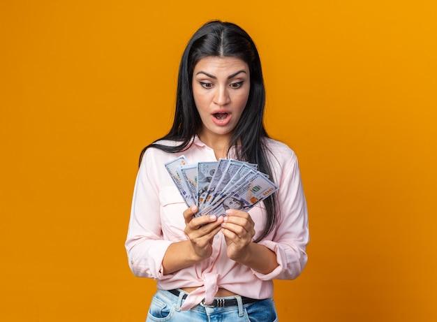 Молодая красивая женщина в повседневной одежде, держащая наличные, глядя на деньги, изумлена и удивлена