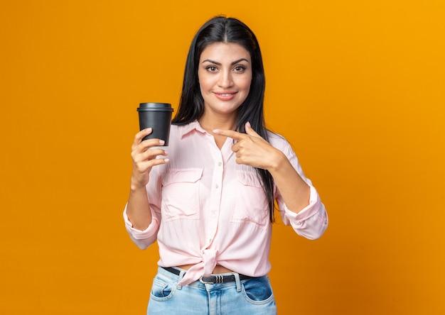 집게 손가락으로 가리키는 커피 컵을 들고 캐주얼 옷을 입은 젊은 아름다운 여성이 주황색 벽 위에 자신감 있게 서서 웃고 있다