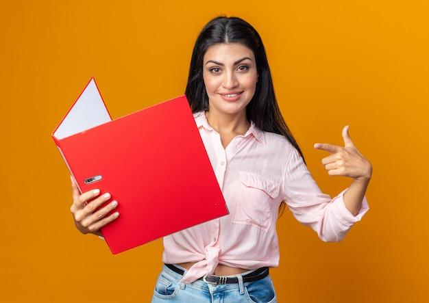 폴더를 들고 있는 캐주얼 옷을 입은 젊고 아름다운 여성은 주황색 벽 위에 서 있는 폴더를 검지 손가락으로 가리키며 자신감 있게 웃고 있습니다.