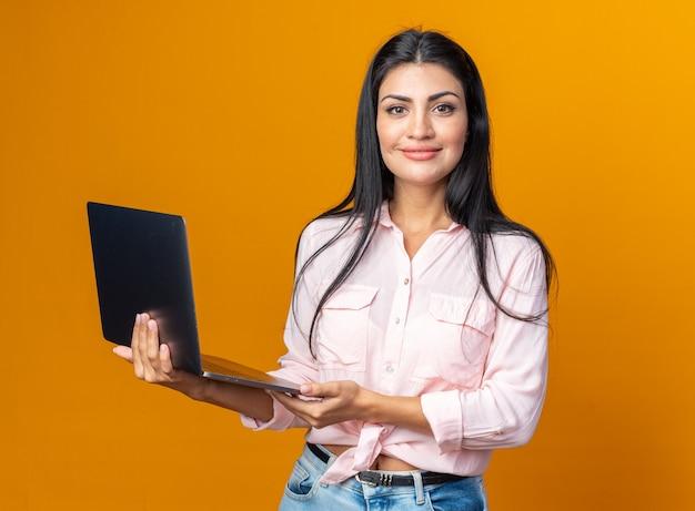 노트북을 들고 있는 캐주얼한 옷을 입은 젊고 아름다운 여성이 주황색 벽 위에 자신감 있게 서서 웃고 있는 앞을 바라보며 행복하고 긍정적입니다.