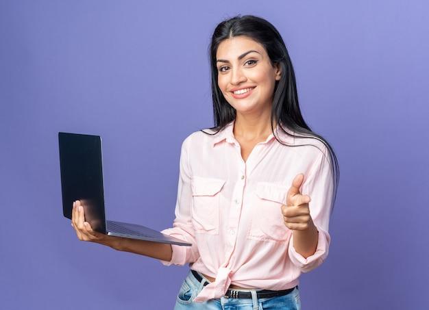 파란색 위에 밝게 웃고 있는 검지 손가락으로 노트북을 가리키는 캐주얼 옷을 입은 젊은 미녀