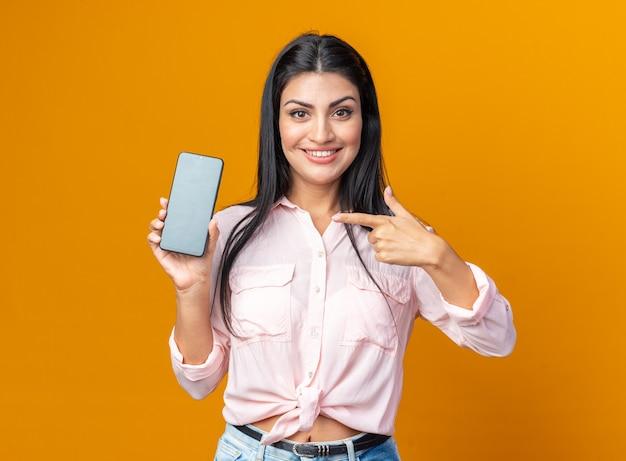 검지 손가락으로 스마트폰을 가리키는 캐주얼 옷을 입은 젊고 아름다운 여성은 주황색 벽 위에 서서 웃고 있는 앞을 바라보며 행복하고 긍정적입니다.