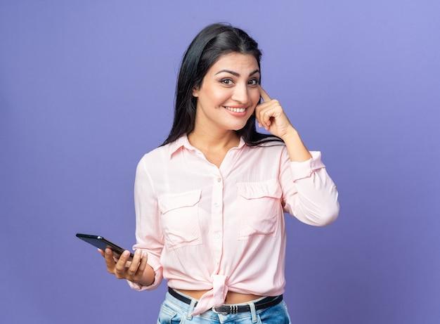 스마트폰을 들고 캐주얼 옷을 입은 젊고 아름다운 여성은 파란색으로 행복하고 긍정적인 미소를 짓고 있습니다.
