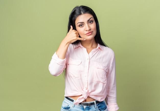 캐주얼 옷을 입은 젊고 아름다운 여성이 앞을 바라보며 자신감을 갖고 녹색 벽 위에 서서 나에게 몸짓을 하고 있다