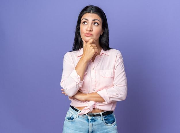 Молодая красивая женщина в повседневной одежде смотрит вверх, положив руку на подбородок, думает с задумчивым выражением лица