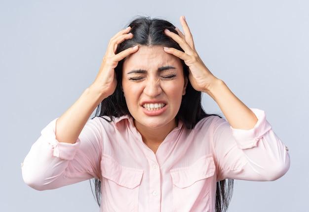 Молодая красивая женщина в повседневной одежде тянет за волосы с разочарованным выражением лица, стоя у белой стены