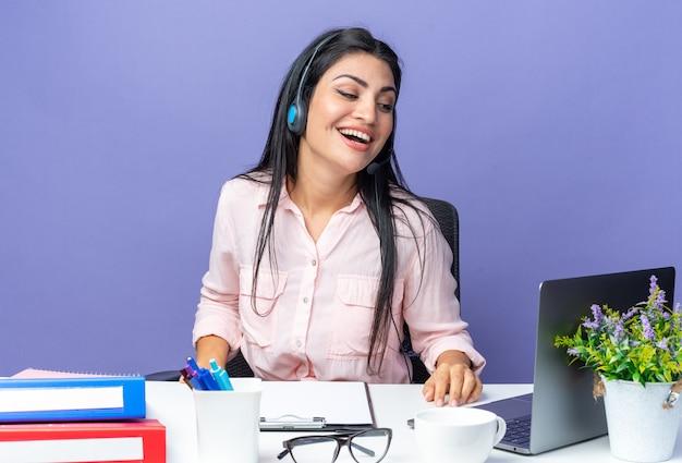 마이크가 달린 헤드셋을 끼고 평상복을 입은 젊고 아름다운 여성이 파란색 노트북을 들고 테이블에 앉아 행복하고 긍정적인 미소를 짓고 있습니다