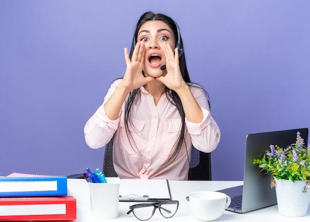カジュアルな服を着た若い美しい女性は、オフィスで働いている青い壁の上のラップトップでテーブルに座って口に手を握ってマイクを叫んでヘッドセットを身に着けています