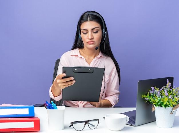 헤드폰과 마이크를 들고 클립보드를 들고 있는 캐주얼 옷을 입은 젊고 아름다운 여성이 파란색 노트북을 들고 탁자에 앉아 진지한 얼굴로 그것을 바라보고 있습니다.
