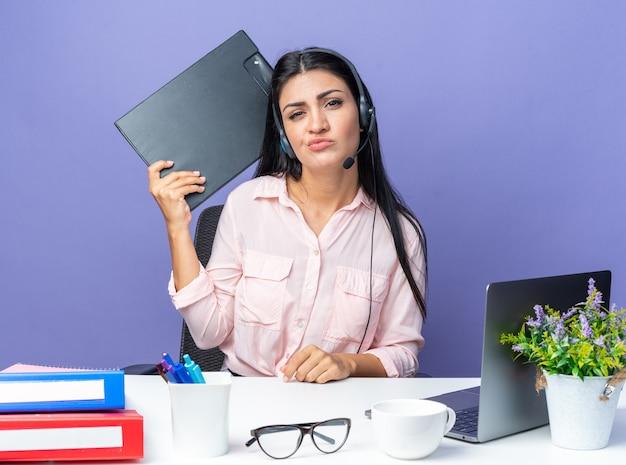 헤드폰과 마이크를 들고 클립보드를 들고 있는 평상복을 입은 젊고 아름다운 여성은 사무실에서 일하는 파란색 벽 위에 노트북을 들고 탁자에 앉아 혼란스럽고 불쾌해 보입니다.