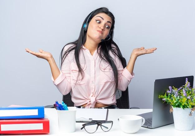 헤드폰과 마이크가 있는 평상복을 입은 젊은 미녀는 사무실에서 일하는 흰 벽 위에 노트북을 들고 탁자에 앉아 양쪽 팔을 벌리고 있는 혼란스러워 보였다