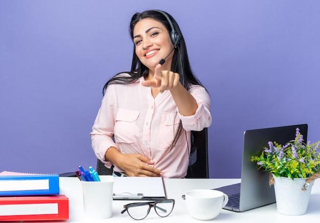 헤드폰과 집게 손가락으로 가리키는 마이크가 있는 캐주얼한 옷을 입은 젊은 미녀는 사무실에서 일하는 파란색 벽 너머로 노트북을 들고 탁자에 앉아 자신감 있게 웃고 있다
