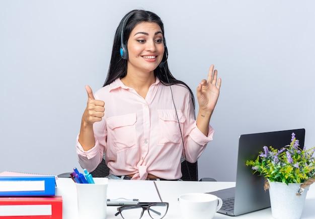 헤드폰과 마이크가 있는 평상복 차림의 젊은 미녀가 책상에 앉아 노트북을 들고 행복하고 사무실에서 일하는 흰 벽 너머로 웃고 있다