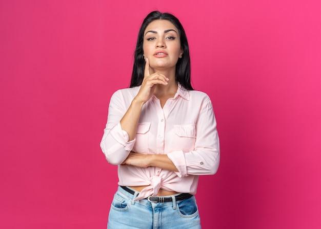 ピンクの壁の上に立っているスマートな顔に笑顔で真剣な自信を持って表情とカジュアルな服を着た若い美しい女性