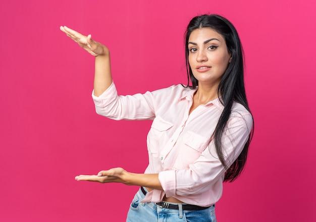 손으로 큰 몸짓을 보여주는 진지한 얼굴로 평상복을 입은 젊은 아름다운 여성, 분홍색 벽 위에 서 있는 측정 기호 개념