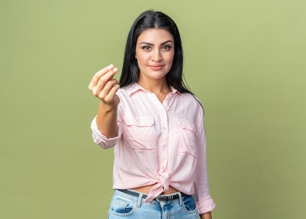 Молодая красивая женщина в повседневной одежде с серьезным лицом показывает денежный жест, потирая пальцы, стоя на зеленом