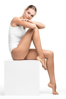 白い表面に座っている綿の下着の若い美しい女性