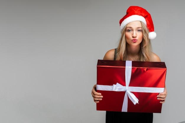 Молодая красивая женщина в платье и новогодней шапке держит подарок и улыбается, картина изолирована на серой стене