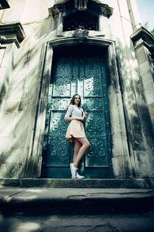 오래 된 출입구 근처에 서 드레스와 가죽 재킷에 젊은 아름 다운 여자