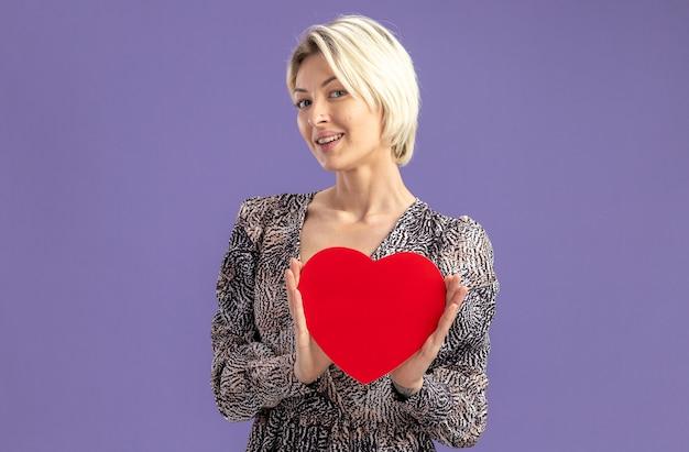 紫色の背景の上に立って元気に幸せでポジティブなバレンタインデーのコンセプトに笑みを浮かべてカメラを見て段ボールから作られた心を保持しているドレスの若い美しい女性