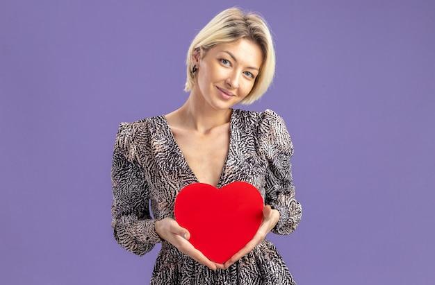 紫色の壁の上に立っている幸せそうな顔のバレンタインデーのコンセプトに笑顔で段ボールから作られた心を保持しているドレスの若い美しい女性